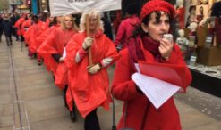 Women march wearing red ponchos and holding a placard saying: 'Dead Women Walking: Domestic Violence Murder March