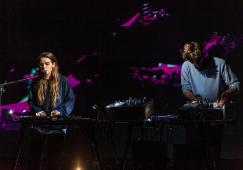 Image of the musical duo Hyperdawn, a man and a woman stood next to each other. The woman is turning dials on a synthesiser and singing into a microphone. The man is also turning dials on a synthesiser.