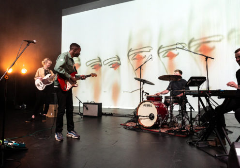 Image of the band Nii performing onstage at Art School Live. Consists of a woman playing bass, a man playing guitar and singing, a man playing the drums, and a man sat playing the keyboard.