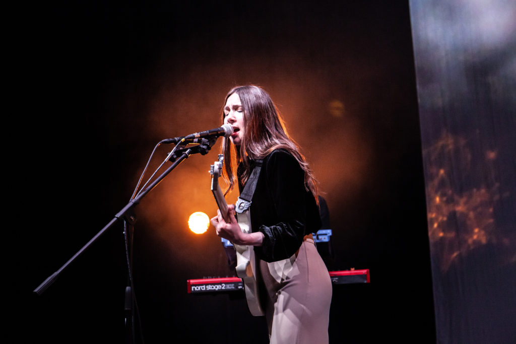 Image of Natalie McCool stood playing a white guitar and singing into a microphone.