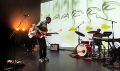 Image of three people. Nii playing the guitar, Tom playing the drums, Amanda playing the bass guitar.